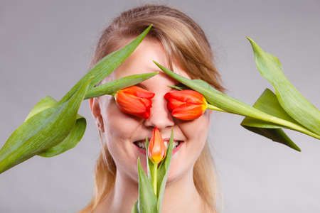 blinded: Beauty nature flora symbolism concept. Blonde girl blinded by flowers. Young female covering her eyes with tulips. Stock Photo