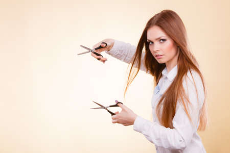 dual: Irresponsibility danger haircut coiffure care beauty concept. Passionate female hairdresser. Cheerful lady dual wielding scissors showing her work tools normal and thinning shears Stock Photo