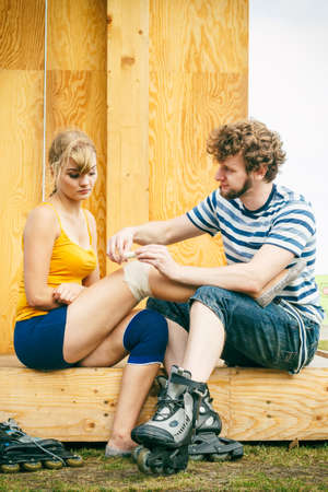 skaters: Sport injury. Couple of skaters outdoor. Young woman suffering from leg pain after taking a fall on the asphalt, man is helping bandaging her injured knee Stock Photo