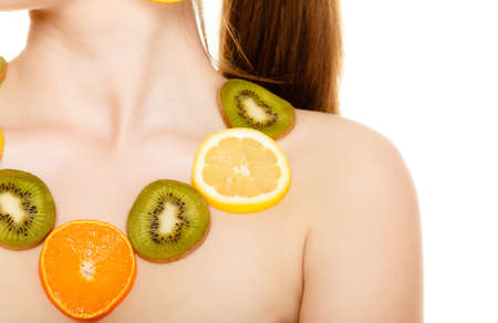 recommending: Diet. Happy girl with necklace of fresh citrus fruits isolated on white. Young woman recommending healthy food and nutrition. Stock Photo