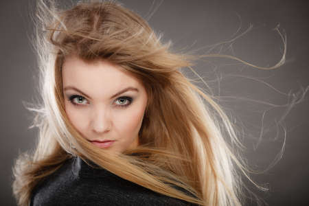 amazing stunning: Hairstyle and haircare concept. Portrait of blonde charming attractive young lady with open waving hair. Woman with healthy and beauty hairdo coiffure. Stock Photo