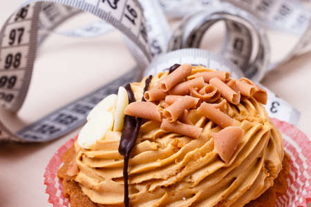 gluttony: Appetite and gluttony concept. Fattening problem. Cake cupcake with measuring tape on table