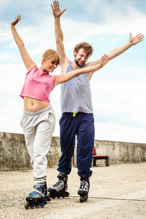 rollerskating: Active young people friends in training suit rollerskating outdoor. Happy woman and man with hands up.
