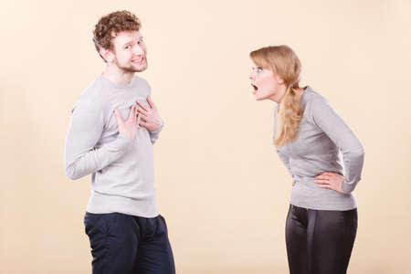 express feelings: Problems in relationship. Young blonde couple arguing and yelling on each other. Emotional way to express bad feelings. Stock Photo
