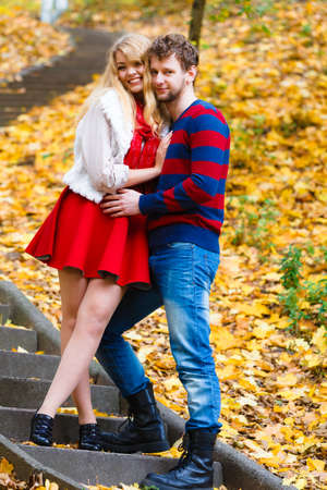 frendship: Spending time with loved ones. Romantic dates in autumnal park. Affection and feelings. Frendship and love. Young couple meet at park having fun on romantic date. Man hold woman in arms hug. Stock Photo
