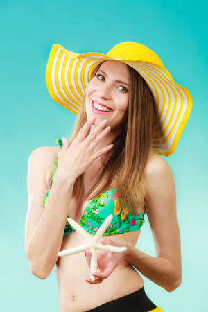 thin shell: Summer holidays concept. Closeup woman in yellow hat bikini holding white shell starfish in hand on vivid blue background
