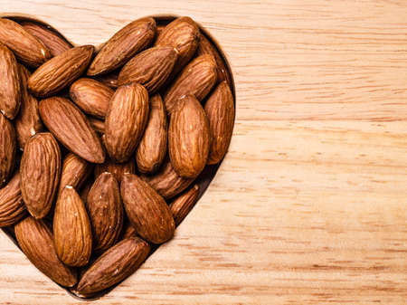 whole food: Whole food, good for health. Heart shaped almonds on wooden surface board background