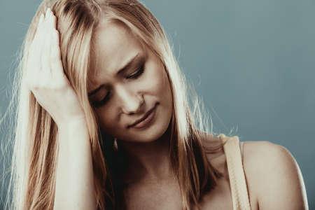 cabeza femenina: Dolor de cabeza, migraña y estrés. Mujer de negocios preocupante molesto niña sufre de dolor de cabeza en gris.