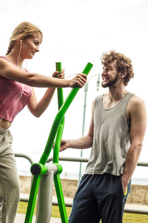active listening: Active woman exercising on elliptical trainer machine and man listening to music. Happy fit sporty girl in training suit working out at outdoor gym. Sport fitness and healthy lifestyle concept.