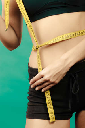 waistline: Weight loss, slim body, healthy lifestyle concept. Fit fitness girl measuring her waistline with measure tape on green Stock Photo