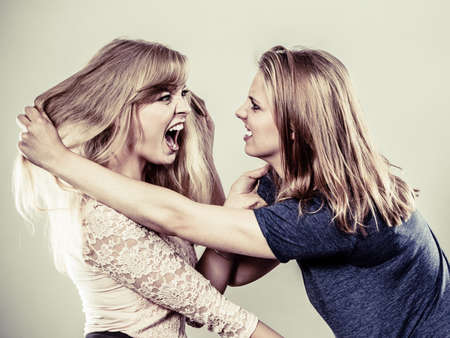 women fighting: Aggressive mad women fighting each other pulling hair. Two young girls struggling win catfight. Violence.