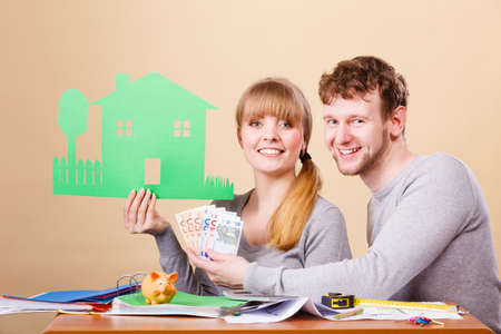 managing money: Family future ownership financial bank property home concept. Young couple managing finances. Girl and boy counting money showing house symbol.