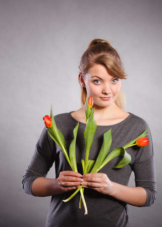 adoring: People and flowers. Girl love nature holding red green tulip spring flower. Woman adoring natural environment.