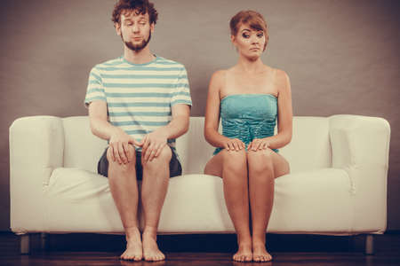 shy woman: Relationship concept. Shy woman and man sitting close to each other on the couch.