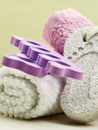 smoothen: Foot care. Pedicure accessories set tools : pumice with footprint, towel, toe separators closeup