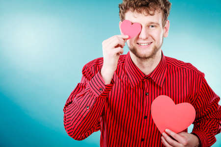 persuade: Love and help from people. Charming lovely man with two red paper hearts persuade to be good helpful hopeful. Valentines Day or charity concept. Stock Photo