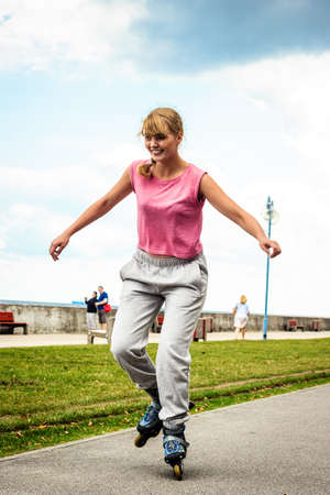 roller blade: Active young woman in training suit rollerskating outdoor. Happy girl riding enjoying sport. Stock Photo