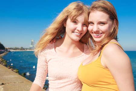 women friendship: Two young women best friends blonde cheerful girls having fun outdoor wind blowing in hair. Summer happiness friendship concept.