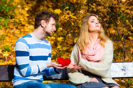 Confessing love and affection with romantic gesture. Rejection and disapproval. Negative reaction. Pair sit on bench in park man hold plush heart showing his emotions girl refuse. Stock Photo