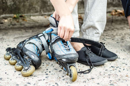 roller blade: Closeup of woman girl putting on roller skates outdoor.