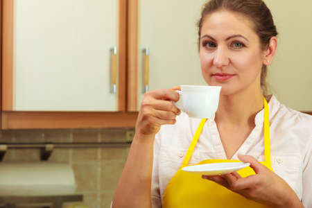 energizing: Mature woman in apron holding cup of coffee in kitchen. Housewife female with hot energizing beverage. Caffeine energy.