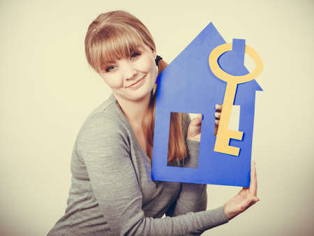 sell house: Selling and buying real estate concept. Young blonde smiling positive female estate agent ready to sell house home. Stock Photo