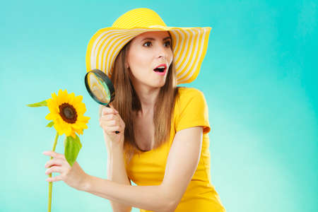 botanist: Botanist woman funny face expression in yellow hat examining flower looking through magnifying glass on blue background