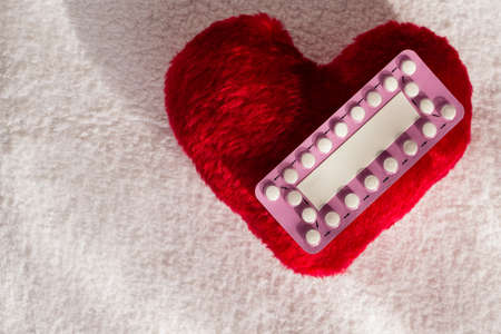 birth prevention: Medicine contraception love and birth control. Oral contraceptive pills on red heart shaped little pillow