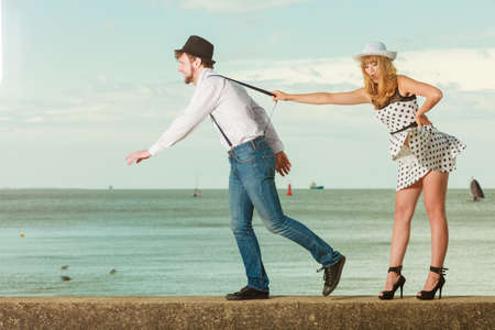 to confess love: holidays love relationship and dating concept - romantic playful couple retro style flirting playing on sea shore, guy running from his girlfriend Stock Photo