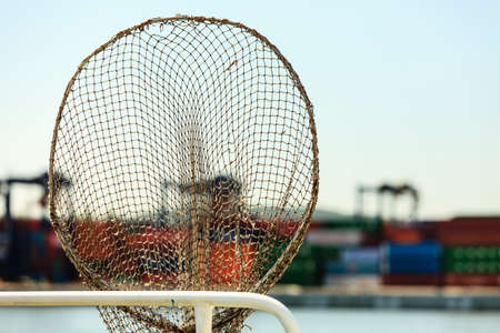commerce and industry: Cargo commerce industry concept.Fishing net in harbour. Fishery tool with containers on pier background.