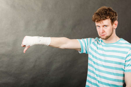 bandaged: Bad news and information. Medicine aspects. Sad unhappy male with bandaged hand showing thumb down sign symbol.