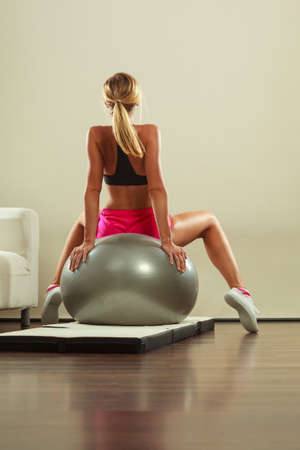 fitball: Sport, training, gym and lifestyle concept. Young attractive slim woman in sportswear doing fitness exercises with fit ball at home
