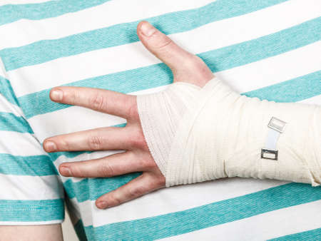 dislocation: Fractures and dislocations concept. Part body male with hand in bandage. Helpful medication for painful palm arm of young man. Stock Photo