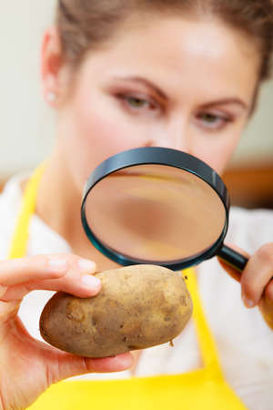 food testing: Mature woman female inspecting testing potato food with magnifying glass.