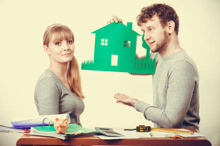 economic rent: Ecology in practical domestic life. People real estate and house concept. Young couple with green ecological paper house happily thinking of future.