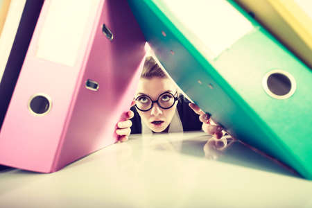 overwork: A lot of work and overwork concept. Terrified young businesswoman secretary with huge stack of binders. Scared accountant surrounded of to much work to do. Stock Photo