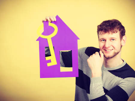stabilization: Dream about stabilization and family. Young man with paper house and big key. Dreaming boy full of plans ideas. New flat apartment.