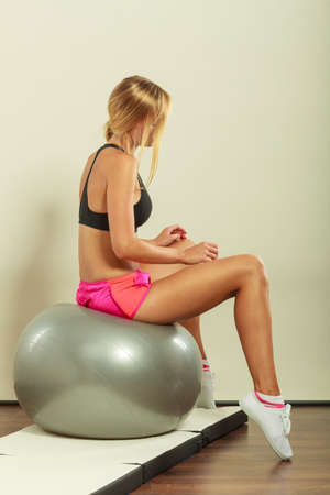 fit ball: Sport, training, gym and lifestyle concept. Young attractive slim woman in sportswear doing fitness exercises with fit ball at home