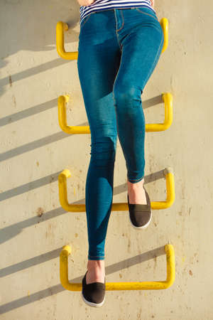 Fashion and people concept. Woman legs in denim trousers casual style outdoor industrial wall background Stock Photo