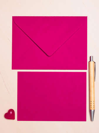 notecard: Pink blank sheet of paper with envelope and little heart, pen on wooden surface. Background for valentines day or wedding card.
