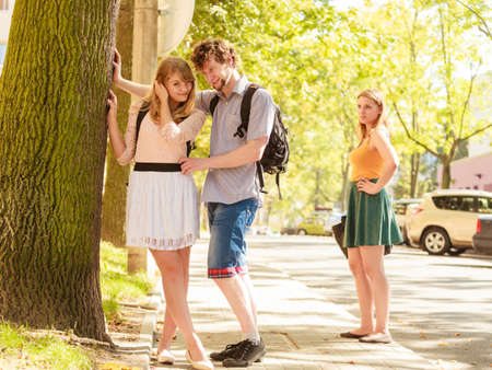 mistrust: Jealous girl looking at flirting couple outdoor. Happy young woman and man couple dating. Summer romance affair.
