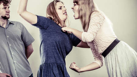 wooing: Aggressive mad women fighting over man. Young jealous girls wooing guy. Violence.