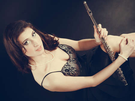 transverse: Music performance. Stunning elegant young lady with transverse flute instrument on black. Woman preparing to her solo show Stock Photo