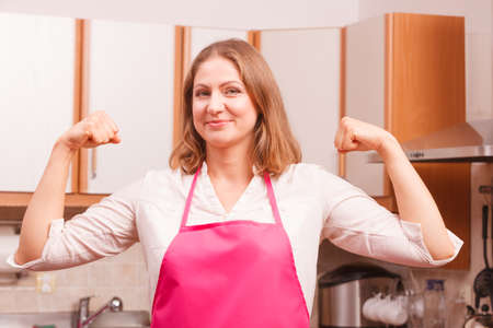 woman hands up: Happy successful and cheerful woman wearing pink apron. Smiling housewife making winning fists hands up gesture in kitchen. Positive emotion.