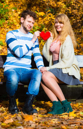 confess: Expressing feelings and affection. Confess love with romantic gesture. Young couple sit on bench in park holding plush heart smiling and sharing good emotions. Stock Photo