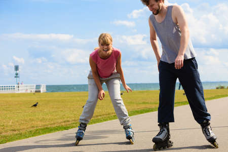 boy skating: Love dating leisure romance relax concept. Cheerful couple enjoying ride together. Young girl and boy skating on rollerblades in park near sea.