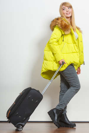 warm jacket: Young woman in warm jacket with suitcase. Gorgeous blonde tourist travel girl. Tourism.