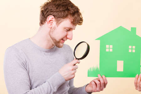 youthful: Ownership details tools deals contract concept. Young man with person and house. Youthful male and someone looking at home through magnifying glass. Stock Photo