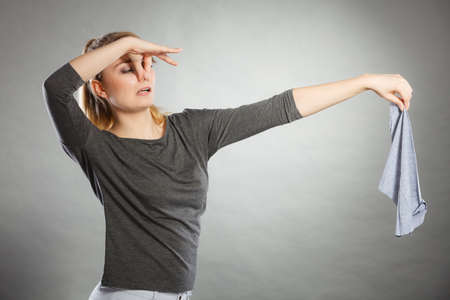 La suciedad olor concepto olor higiene. Disgustado mujer sostiene trapo sucio. Señora mantener el tejido mal olor en la distancia.