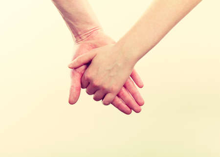 two minds: Symbols of love. Couple showing their connection and feelings by holding their hands strongly. Body language as expression of mind state.